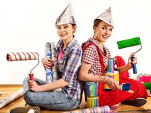 Repair home women holding painting tools roller for wallpaper. Happy girls wearing newspaper hat renovation apartment in room. Unification of friends due to royalty free stock photos