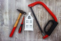 Repair in house concept. Construction tools and white house model on wooden background. royalty free stock photo