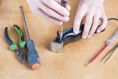 Repair of household appliances. Repairman with screwdriver on the table parsed shearer Royalty Free Stock Photography
