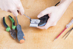 Repair of household appliances. Repairman with screwdriver on the table parsed shearer Stock Images