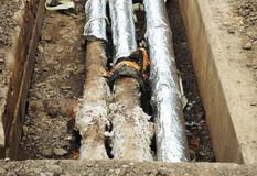 Repair, insulation and replacement of city sewer on the street.  Pipes for water in an earthen trench. Stock Photos