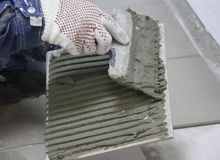 Repair - interior decoration. Laying of floor ceramic tiles. Men`s hands tiler in gloves with  spatula spread  cement mortar on. Repair - interior decoration Royalty Free Stock Images