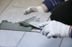 Repair - interior decoration. Laying of floor ceramic tiles. Men`s hands tiler in gloves with  spatula spread  cement mortar on. Repair - interior decoration Royalty Free Stock Photos
