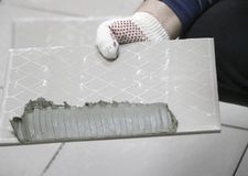 Repair - interior decoration. Laying of floor ceramic tiles. Men`s hands tiler in gloves with  spatula spread  cement mortar on. Repair - interior decoration Stock Photography