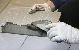 Repair - interior decoration. Laying of floor ceramic tiles. Men`s hands tiler in gloves with  spatula spread  cement mortar on. Repair - interior decoration Royalty Free Stock Image