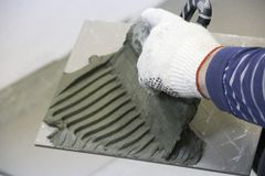 Repair - interior decoration. Laying of floor ceramic tiles. Men`s hands tiler in gloves with  spatula spread  cement mortar on. Repair - interior decoration Stock Images