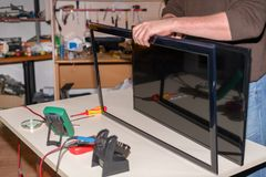 Repair LCD TV, disassembly LED panel of television screen stock photography