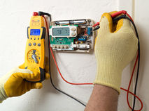 Repair man. Hands of a man wearing gloves holding tools fixing an thermostat Stock Images