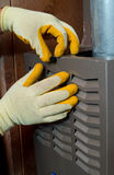 Repair man. Hands of a man wearing gloves holding tools fixing a furnace Royalty Free Stock Photos