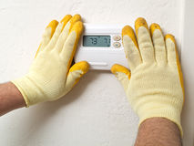 Repair man. Hands of a man wearing gloves holding tools fixing a thermostat Royalty Free Stock Photo