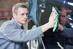 Repair man worker polishing automobile car body in garage Stock Photos