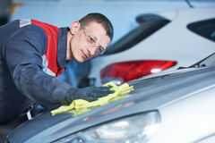 Repair man worker polishing automobile car body in garage Royalty Free Stock Images