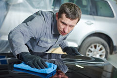 Repair man worker polishing automobile car body in garage Royalty Free Stock Photography