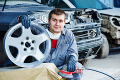 Repair mechanic worker with light alloy car wheel disk rim Royalty Free Stock Photos