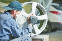 Repair mechanic worker with light alloy car wheel disk rim. Auto repair mechanic worker with light alloy car wheel disk rim during refurbish at garage service stock photography