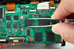 Repair microchip on electronic board photo DSLR camera in service Royalty Free Stock Images