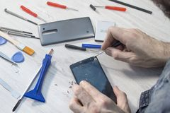 Repair of a mobile phone, smartphone. Special tools lie on the countertop with the elements of the phone. Replacing broken glass on a mobile phone in a mobile royalty free stock images