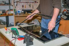 Repair of modern TV, disassembling the screen to replace the LCD matrix. stock photos