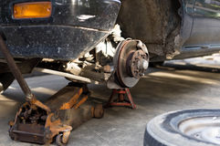 Repair old car brake disk of the wheel hub with jack Stock Photo