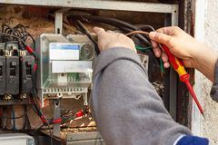 Repair of old electrical switchgear. An electrician replaces old electrical wiring devices. Stock Image