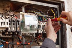 Repair of old electrical switchgear. An electrician replaces old electrical wiring devices. Royalty Free Stock Photo