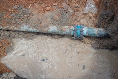 Repair the plumbing broken pipe and water flow in hole.  stock image