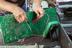 Repair of a power supply unit in the service center, fault diagnosis by measuring devices.  royalty free stock image