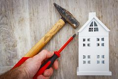 Repair and reconstruction of house concept. hammer, screwdriver in hand of builder and model of house on wooden background. Stock Image