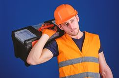 Repair and renovation concept. Worker, repairer, repairman, strong builder on thoughtful face carries toolbox on. Shoulder, ready to work. Man in helmet, hard royalty free stock image