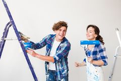 Repair, renovation and love couple concept - young family doing redecoration and painting walls together and laughing. royalty free stock photography