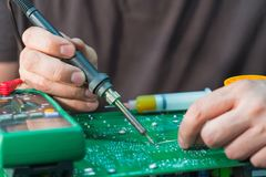 Repair and restore PCB of a uninterruptible power supply unit. Soldering of electronic components Stock Photos