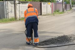 Repair of roads. the worker is repairing the road. The man is working with a jackhammer. Repair of roads. the worker is repairing the road. The man is working Royalty Free Stock Images
