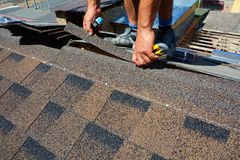 Repair of a Roofing from shingles. Roofer cutting roofing felt or bitumen during waterproofing works. Roof Shingles - Roofing. Bitumen tile roof royalty free stock image