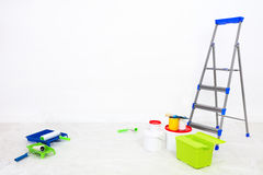 Repair in the room. stepladder and paint at blank wall Royalty Free Stock Photo