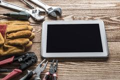 Repair service request. Variety of tools of builder and tablet pc on wooden texture table royalty free stock photography