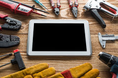 Repair service request. Variety of tools of builder and tablet pc on wooden texture table stock photography