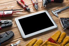 Repair service request. Variety of tools of builder and tablet pc on wooden texture table royalty free stock image