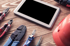 Repair service request. Variety of tools of builder and tablet pc on wooden texture table stock images