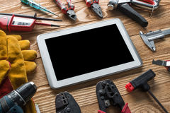 Repair service request. Variety of tools of builder and tablet pc on wooden texture table royalty free stock photos