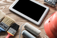 Repair service request. Variety of tools of builder and tablet pc on wooden texture table stock photo