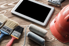 Repair service request. Variety of tools of builder and tablet pc on wooden texture table royalty free stock photo