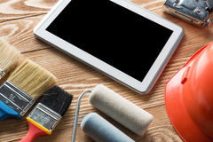 Repair service request. Variety of tools of builder and tablet pc on wooden texture table stock image