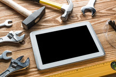 Repair service request. Variety of tools of builder and tablet pc on wooden texture table stock photos