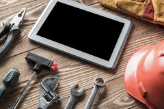Repair service request. Variety of tools of builder and tablet pc on wooden texture table royalty free stock images