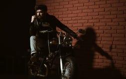 Repair shop. bearded man biker in repair shop. repair shop or biker club. repair shop garage. bike is his life. Repair shop. bearded man biker in repair shop stock image