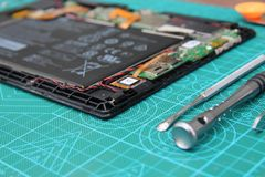 Repair the tablet on the table with tools on a green substrate royalty free stock photos