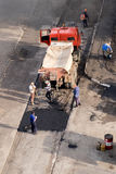 Repair team restores the pavement. A team of workers lays new asphalt covering on road surface Stock Photography