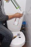 Repair toilet cistern. Plumber repairing the drain valve in the toilet tank Stock Image