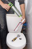 Repair toilet cistern. Plumber repairing the drain valve in the toilet tank Royalty Free Stock Photo