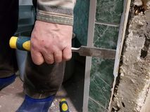 Repair - tool chisel in the hands of the builder. Or finisher stock photos